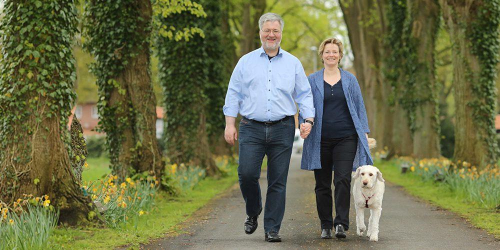 Stephan Albani und seine Frau Angela Albani laufen mit ihrem Hund durch eine Alee