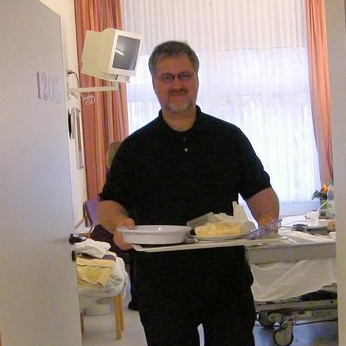 Stephan Albani verlässt ein Patientenzimmer mit einem Tablett in der Hand