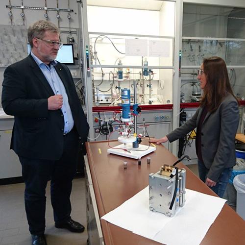 Herr Albani und eine Forscherin unterhalten sich n einem Labor