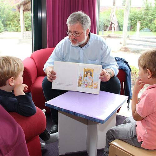 Stephan Albani zeigt Kindern die Abbildungen in einem Kinderbuch