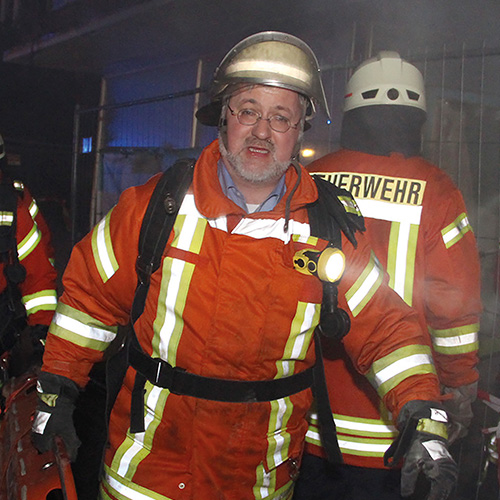 Stephan Albani in Feuerwehrmontur trägt eine Rettungsbahre