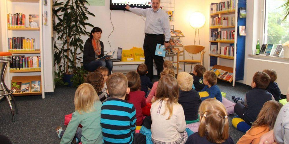 """Stephan Albani liest einer Gruppe Kindergartenkinder beim Aktionstag """"Lesestart"""" vor"""