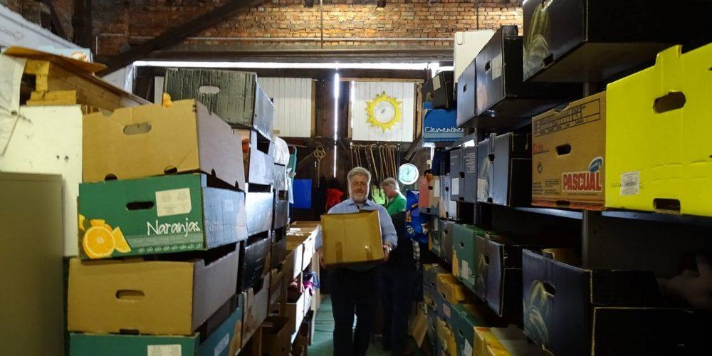 Albani trägt frisch eingetroffene Kartons an ihren Lagerort.