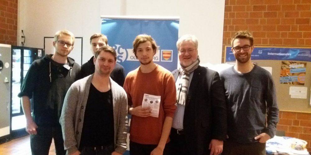 Stephan ALbani und das RCVDS-Team stehen am Wahlkampfstand in der Universität Oldenburg- Im Hintergrund ein blauer Banner mit der Aufschrift RCDS Oldenburg.