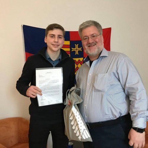 Schülerpraktikant Timo Pundt erhält von Stephan Albani sein Zeugnis. Im Hintergrund die Ammerland-Flagge.