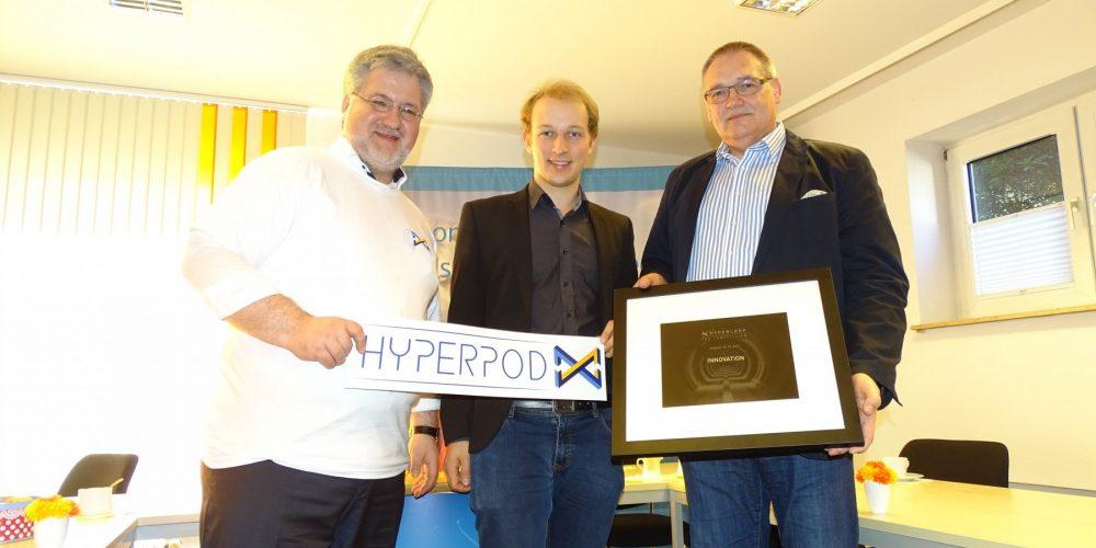 Erinnerungsfoto mit Geschenkübergabe. Stephan Albani trägt ein HyperpodX-Team-T-Shirt.