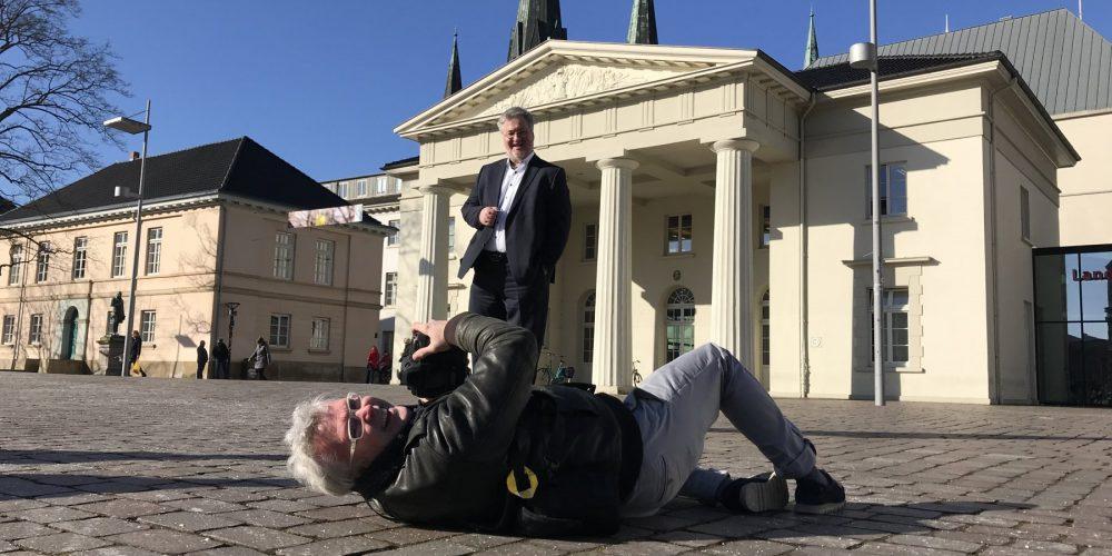 Torsten von Reeken liegt auf dem Boden vor der Alten Wache auf dem Schlossplatz Oldenburg und fotografiert in akrobatischer Lage den stehenden Abgeordneten Stephan Albani bei blauem Himmel. Im Hintergrund sind die Türme von St. Lamberti zu sehen.